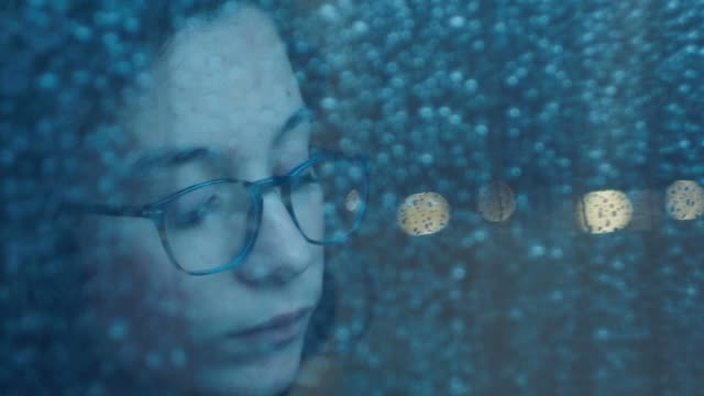 Girl behind window drinking an hot drink cup  in a rainy day. Shot in slowmotion video