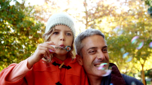 Girl blowing bubbles held by dad outdoors video