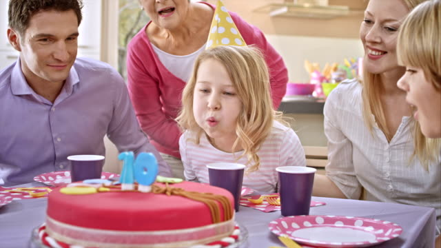 SLO MO girl blowing out the candles on the birthday cake video