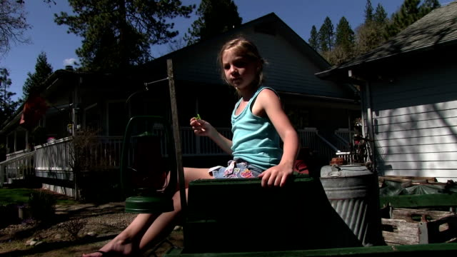 Girl blowing slow motion bubbles on old wagon video