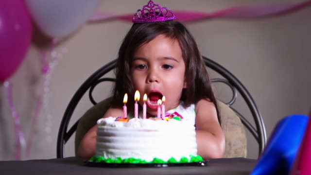 Girl blows out birthday candles on cake video