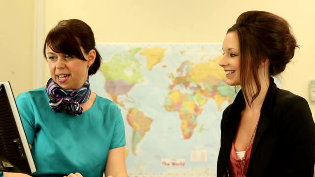 Girl booking a holiday at Travel agents - Dolly video