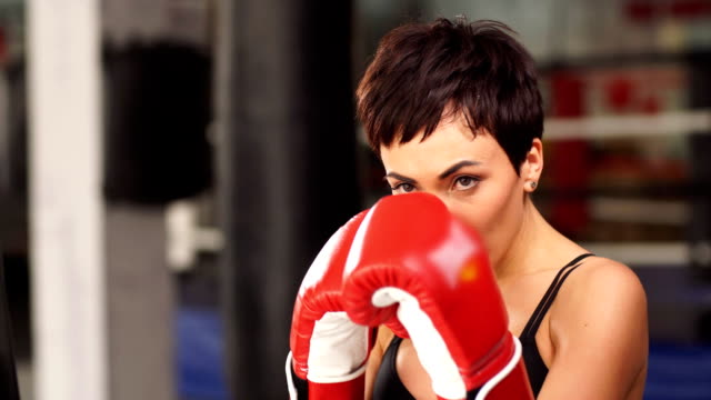 girl boxer trains in red gloves close up - kick boxing video stock e b–roll