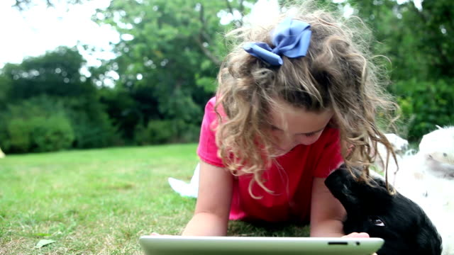 Girl browsing digital tablet being distracted by her dog video