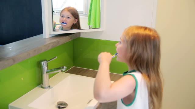 Girl brushing his teeth in the mirror video