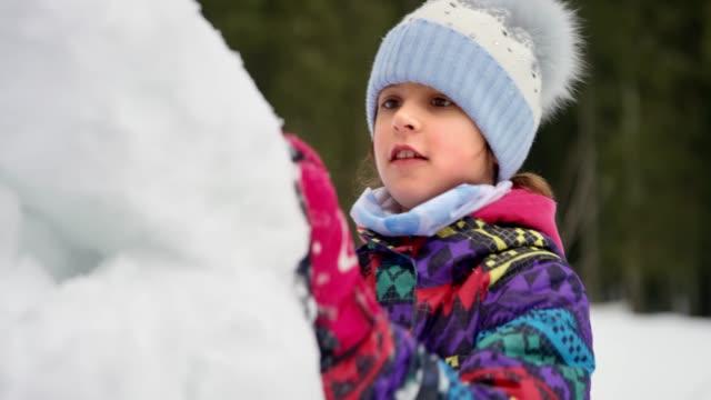 vídeos y material grabado en eventos de stock de slo mo niña construyendo un muñeco de nieve y diversión - snowman