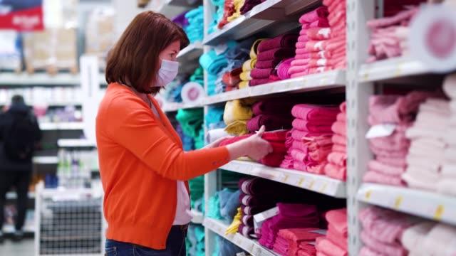 Girl buying bath towel in supermarket during pandemic video