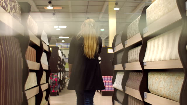 Girl buys a wallpaper in a building store. video