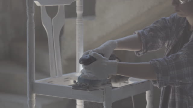 girl carpenter, designer, works with electric tool - levigatrice video stock e b–roll