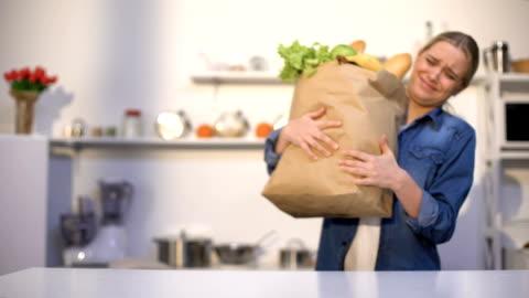 vidéos et rushes de fille transportant le paquet lourd d'épicerie, problèmes avec la livraison, achats hors ligne - lourd