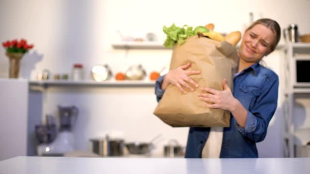 vídeos y material grabado en eventos de stock de chica que lleva un paquete pesado de comestibles, problemas con la entrega, compras fuera de línea - pesado