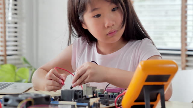 Girl checking circuit board with multimeter at home and building a robot as a school science project.She is very satisfied with her work.Happy smiling girl constructs technical.education, children, technology, science people concept Girl checking circuit board with multimeter at home and building a robot as a school science project.She is very satisfied with her work.Happy smiling girl constructs technical.education, children, technology, science people concept genius stock videos & royalty-free footage