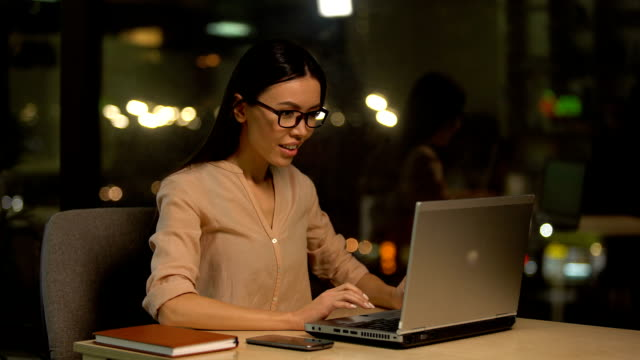 Girl checking email on laptop, extremely happy about hiring on her first job