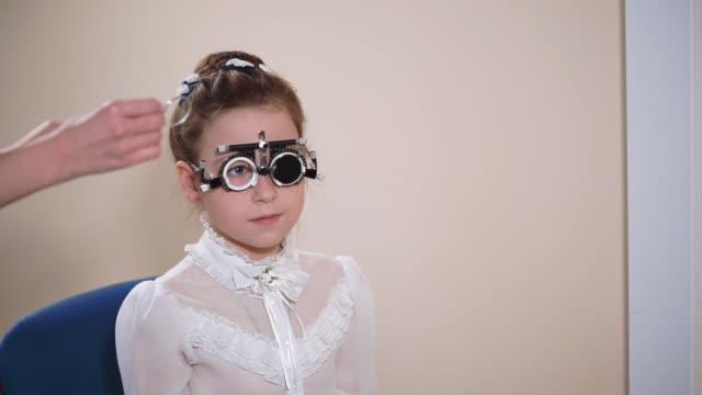 vidéos et rushes de fille de vérifier sa vue à oculist - réfracteur