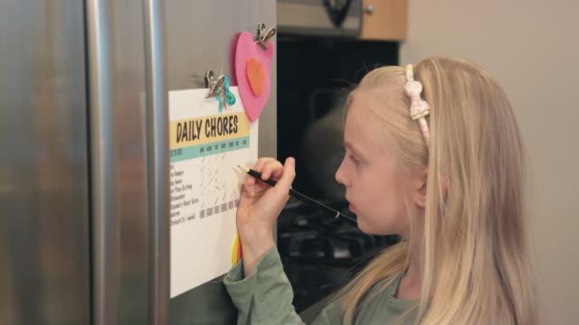 vídeos de stock, filmes e b-roll de menina verifica fora tarefas da lista - afazeres domésticos