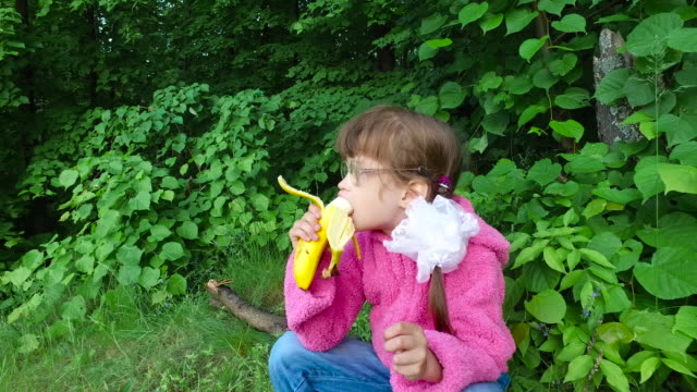 Girl child eats banana in a summer forest. The girl has a good appetite in the fresh air. video