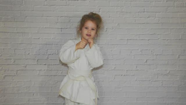 kız, çocuğun bir kimono karate eğitim darbeler ve tebrik çalışır - karate stok videoları ve detay görüntü çekimi