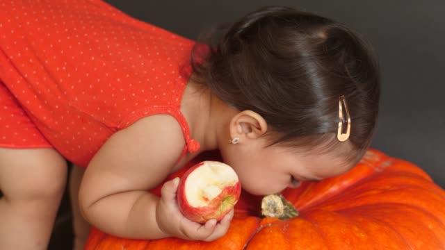 enfant de fille dans un t-shirt rouge mangeant une pomme rouge - Vidéo