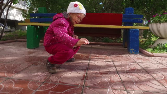 Girl child in glasses draws with chalk on the sidewalk. The pavement is covered with tiles. video