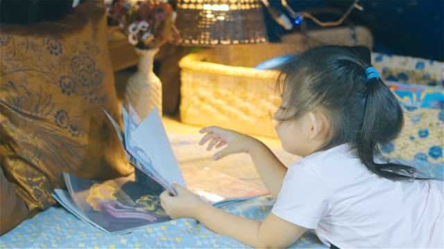 girl child reading kids book in a tent - fiaba video stock e b–roll