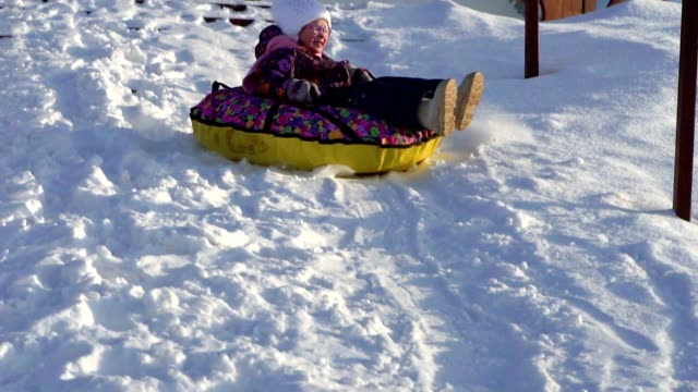 vídeos de stock e filmes b-roll de slow motion:  girl child rolls on a toboggan running on a sled tubing. the child likes to downhill slope in the winter. - roupa quente