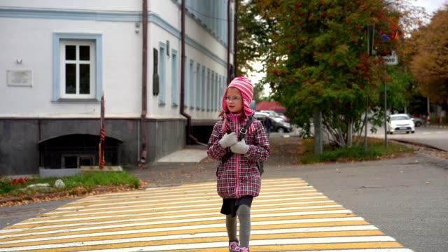 stockvideo's en b-roll-footage met meisje kind het schoolmeisje gaat naar huis na school. het meisje kruist de weg bij de voetgangersoversteekplaats. slow-motion. - oversteekplaats