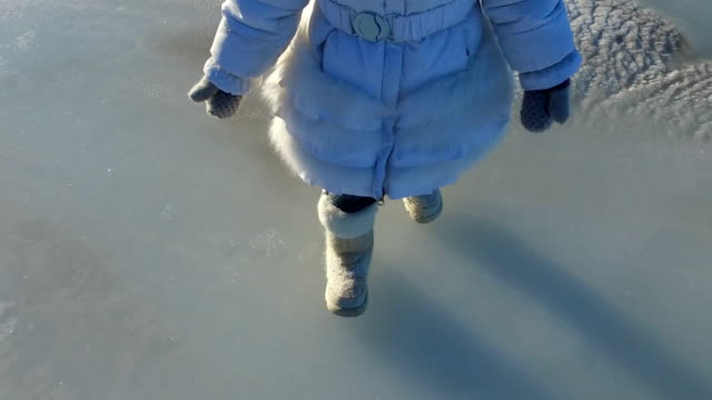 Girl child walks on the ice large lake. Girl is glad that the lake was frozen. The child can now slide on the ice. Sunny frosty winter day. video