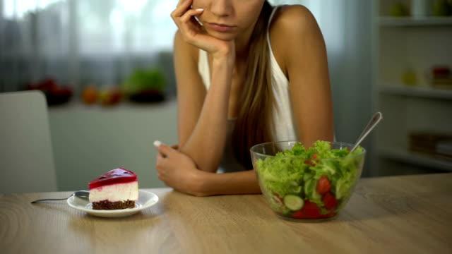 stockvideo's en b-roll-footage met meisje kiest taart in plaats van salade, afgesloten vermoeiend dieet, suiker voor lichaam energie - ongezond leven