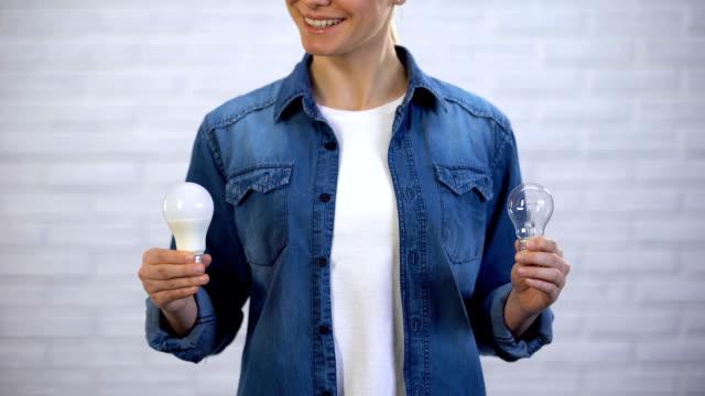 vídeos de stock, filmes e b-roll de menina escolhe poupança de energia bulbo conduzido em vez de lâmpada incandescente, eficiência - led