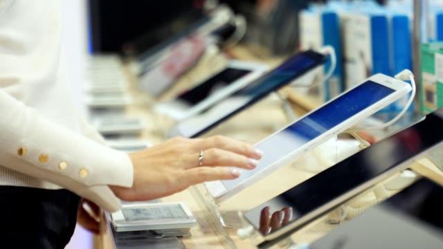 ragazza sceglie prodotti con un tablet al supermercato - industria elettronica video stock e b–roll