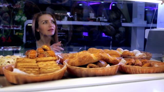 vídeos de stock e filmes b-roll de menina escolher bolos no café do balcão - bolo sobremesa