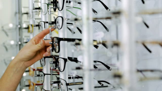 Girl choosing glasses Young woman choosing glasses in optician store eyesight stock videos & royalty-free footage
