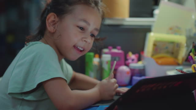 a girl (7-8 years) choosing pencil and doing homework on table in living room - matita colorata video stock e b–roll