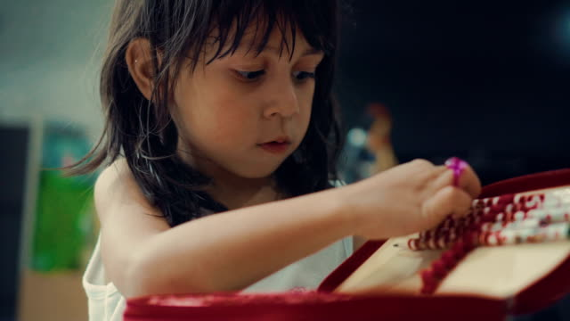 A girl (5-7) choosing pencil and doing homework on table in living room video