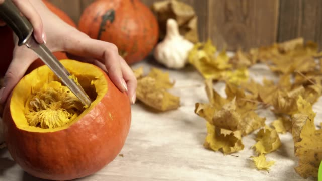 girl cleans out the inside of a pumpkin with a knife - zucca legenaria video stock e b–roll