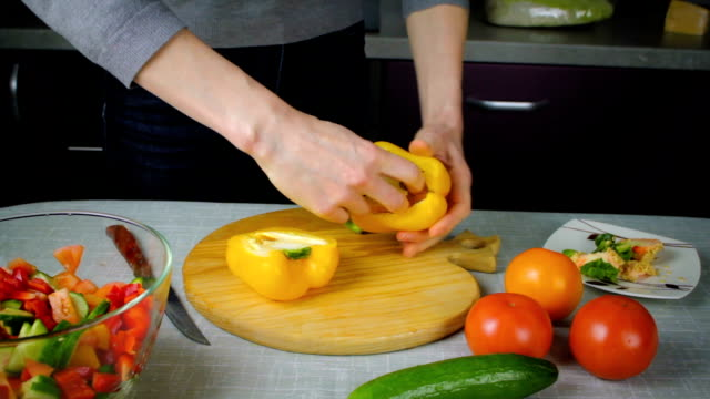 Girl cleans yellow pepper at the board Girl cleans ripe yellow bell pepper at the board in kitchen paprika stock videos & royalty-free footage
