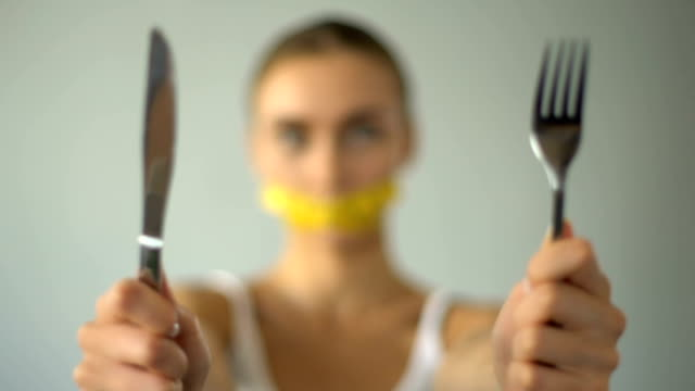 girl closed mouth with tape-line, holding fork and spoon, diet, calorie counting - proibizione video stock e b–roll