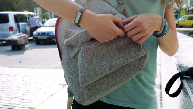 kız sırt çantasında fermuar cebine kapatır. yaz aylarında bir sırt çantası ile şehirde kadın. - sırt çantası stok videoları ve detay görüntü çekimi