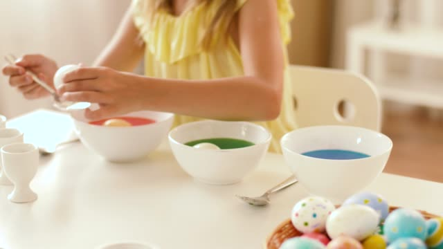 girl coloring easter eggs by liquid dye at home - icona posate video stock e b–roll