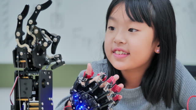 Girl constructs and programmes on computer and building a robot arm as a school science project.She is very satisfied with her work.Education,technology,teamwork,science and people concept.Education Topics - vídeo