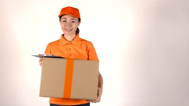 女孩快遞在橙色制服運送大紙板包裹。全高清拍攝, 隔離 - postal worker 個影片檔及 b 捲影像