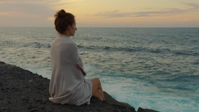 Ein Mädchen, das mit einem Karo bedeckt ist, sitzt auf einem Pier und beobachtet die Meereswellen bei Sonnenuntergang – Video