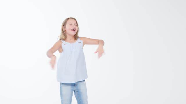 Girl Dancing And Doing Dab Pose Against White Studio Background