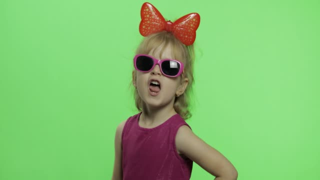 Girl dancing in purple dress, sunglasses and red ribbon on head. Chroma Key