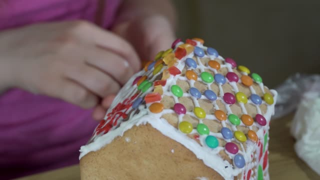 mädchen schmückt ein weihnachts-lebkuchenhaus - lebkuchenhaus stock-videos und b-roll-filmmaterial