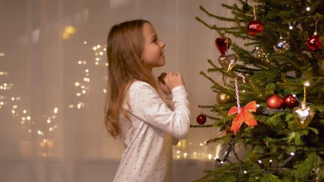 girl decorating christmas tree at home - jodła filmów i materiałów b-roll