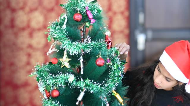 Girl decorating Christmas tree