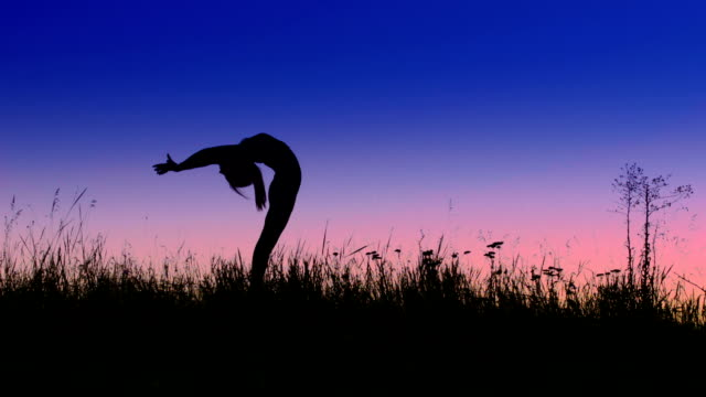 Girl does backbend exercise in evening field video