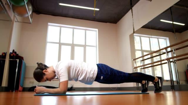 mädchen tun übung plank. steht auf der matte in der mitte der fitness-raum. 4k slow mo - bauholz brett stock-videos und b-roll-filmmaterial