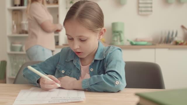 девушка делает домашнее задание дома - covid testing стоковые видео и кадры b-roll